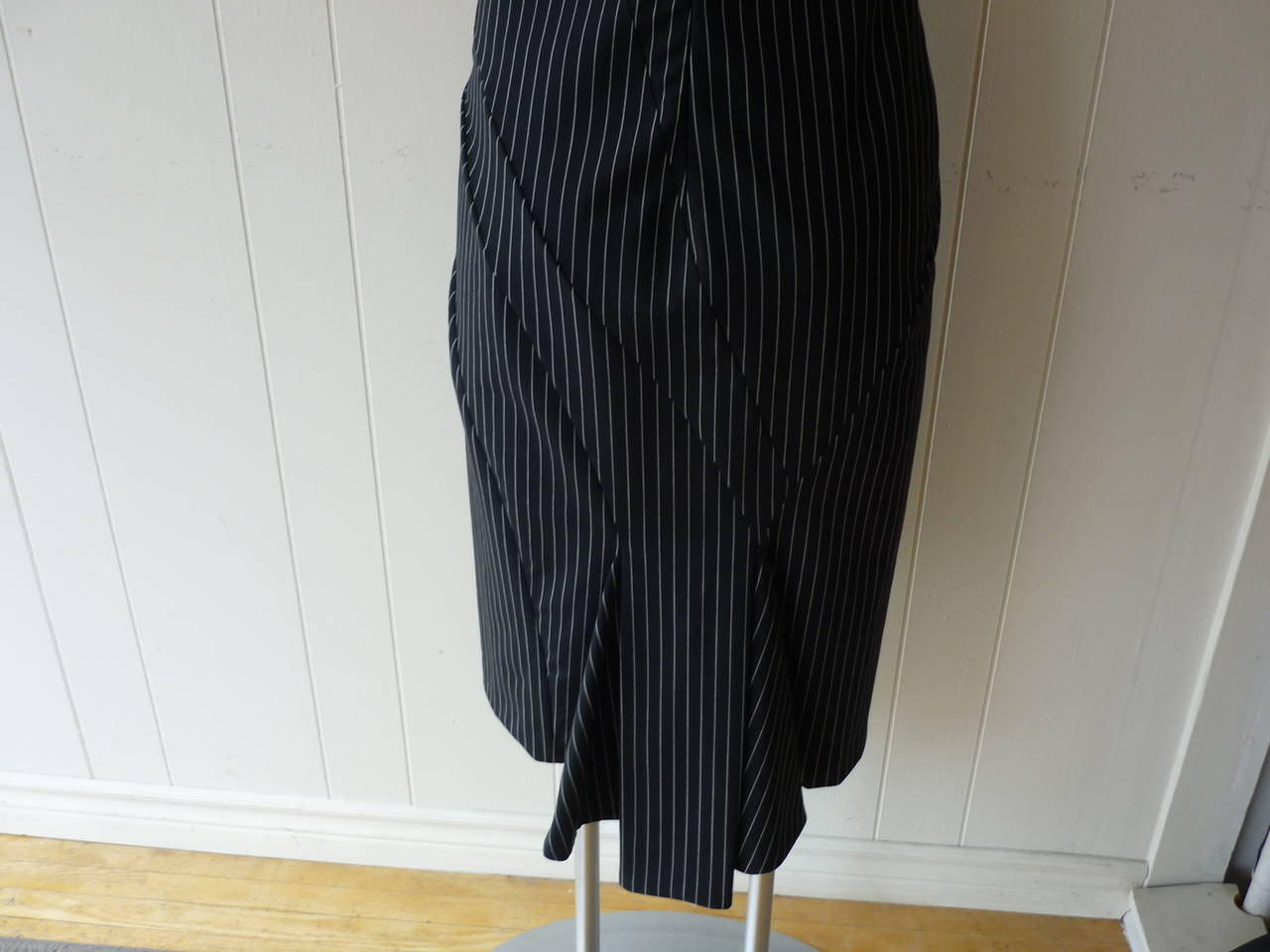 The dress which is black with a white is made of light wool. From the front it looks simple apart from the lovely darting, however, turn it around and it has a magnificent fishtail bottom.