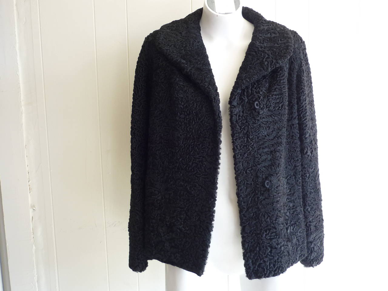Persian Lamb also known as astrakhan, this jacket is in pristine condition with a lovely black lining with a rose design (black and white). There are two vertical slit pockets and gros grain trim on the scalopped bottom as well as the