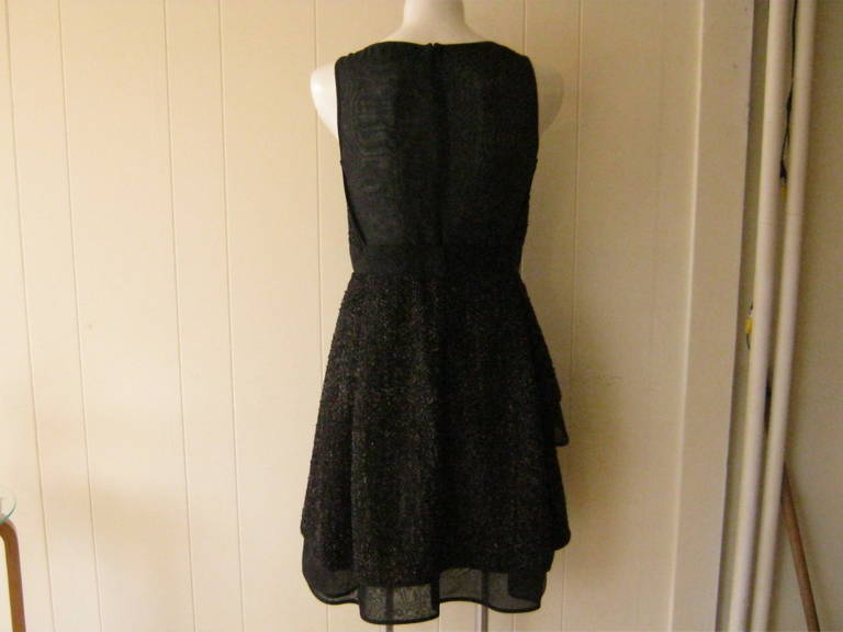 Such an elegant dress with a diamond neckline. The wool flecked boucle material hasa lot of texture and a number of  tiers. For an added touch, the bodice is almost sheer in the back. Look at the additional pictures as I have tried to show all the