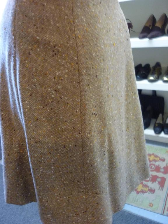 Very nice a-line wool tweed skirt in tones of beige with a hint of orance. Thre is a pleat on the fron which give the impression of a wrap skirt; a big button with a quarter belt; zip closure on the side, and the hem is hand finished.