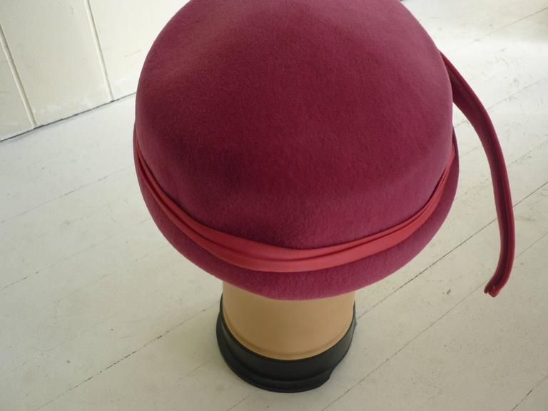 Made of felt, trimmed with satin, with a featherlike adornment, this hat fits snugly on your head.  The underside of the hat has a serpentine silver and gros grain trim.  The hat was made in Italy.