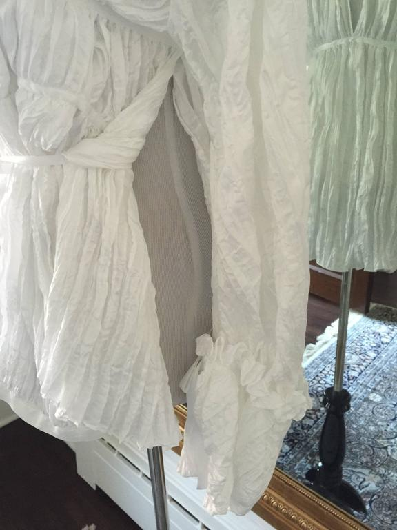 White crinkled ruffled blouse, perfect for this summer to wear with short pants. The blouse has over sized sleeves with a large ruffled collar, and tie front and the back.