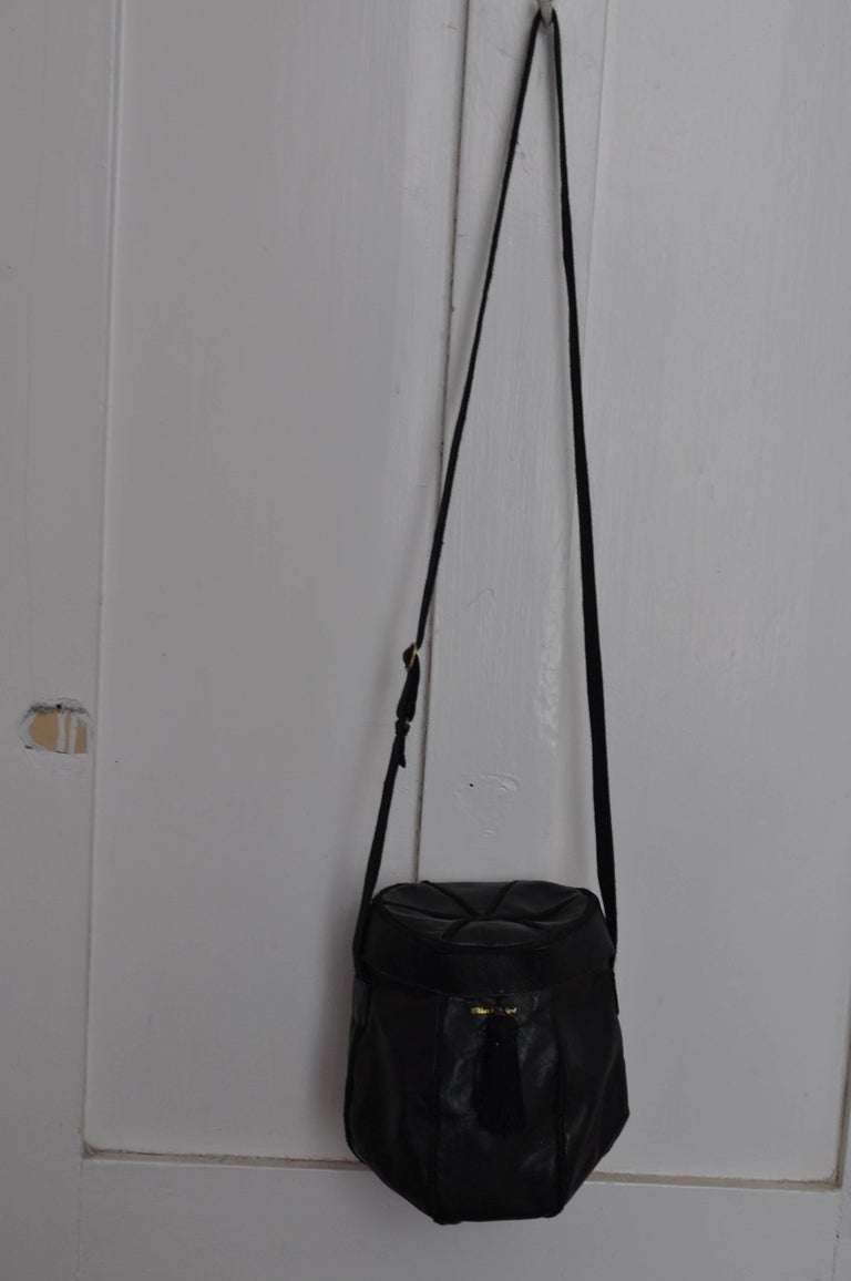This may be a one of a kind purse ordered by the Wilkes Bashford store. It is black; made of a coated material which resembles the texture of lizard;  grosgrain borders; a clasp closure with a tassel, and a ribbed material adjustable crossbody