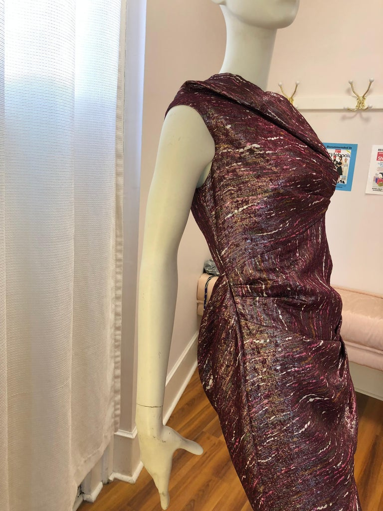 The blend of mainly silk with a bit of polyamide and metallic fibers give this dress a wonderful shine. There is draping back and front, and includes the neckline.  The lining is 100% silk and dress is very light.