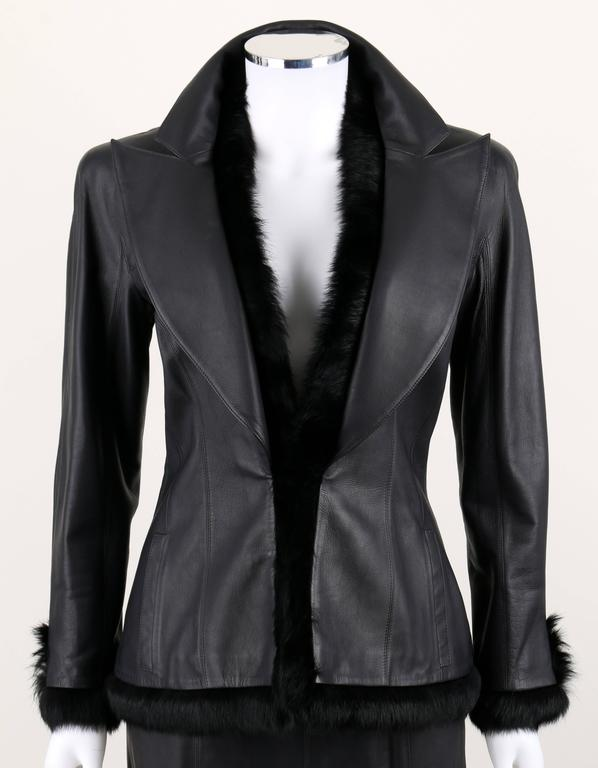 Chanel black genuine lambskin leather skirt suit with black rabbit fur trim.  Jacket has a dramatic lapel.  Fur trim at collar, front placket, hemline and cuffs.  Two pockets.  Closes with single hook/eye at front. Black silk signature lining.