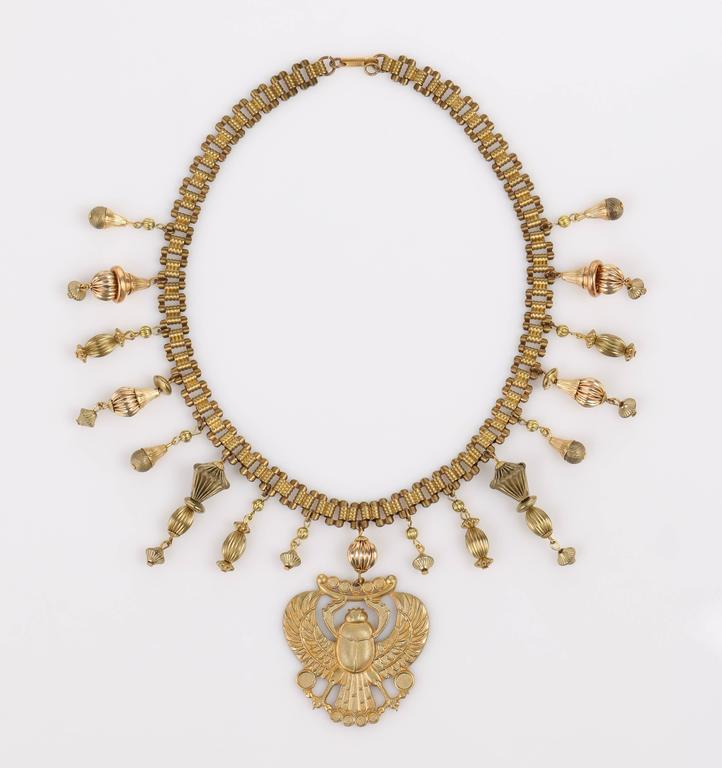 "Late 1970s Miriam Haskell (signed) gold-tone winged scarab large pendant necklace. Chain is curb style with rectangular links joined with grooved connectors that look like stacked beads. Push clasp is marked ""Miriam Haskell"" and ""Patent 3421691""."