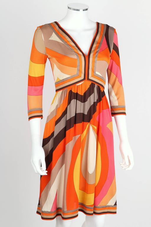 Vintage c.1960s Emilio Pucci orange, pink, brown, gold, and ivory abstract signature print silk jersey dress. Empire waist. V-neckline at front. Three-quarter length sleeves. Above the knee length. Center back zipper closure. Marked Fabric Content: