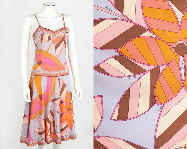 Vintage c.1970s Emilio Pucci cotton jersey drop waist sundress. All over multicolor abstract floral signature print motif. Decorative border on neckline, waist, and hem. Spaghetti straps. Knee length. Full skirt. Zips at side. Marked Fabric Content: