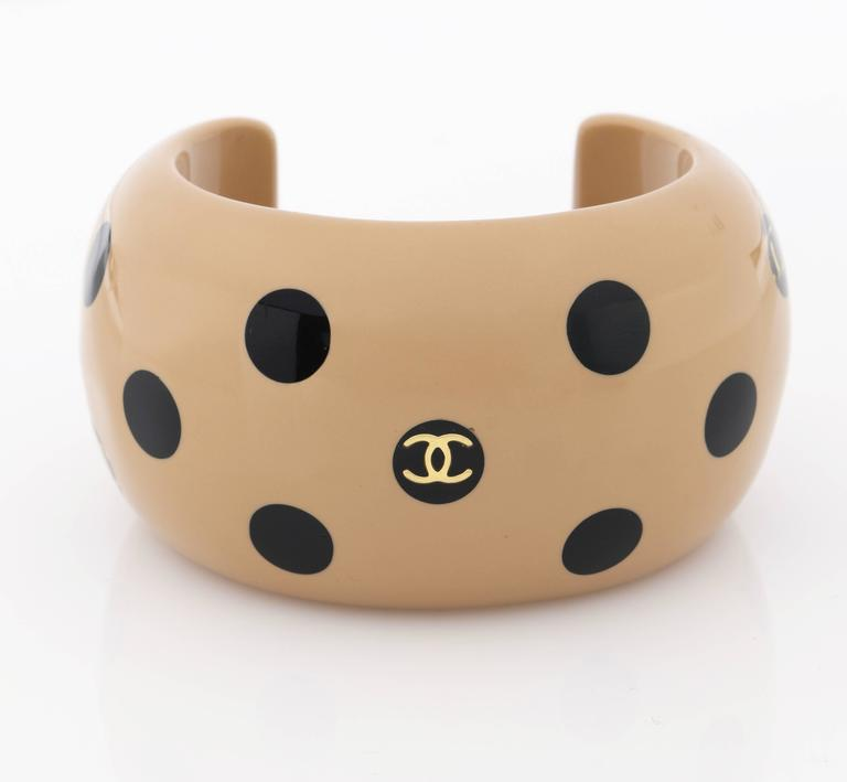 "Chanel Autumn 2000 tan and black polka dot ""CC"" resin/acrylic cuff bracelet.  Cuff is a wide (measures approximately 1 3/4""W) tan/camel colored resin with black polka dots (measure approximately 9mm). Three of the the black polka dots have gold ""CC"""