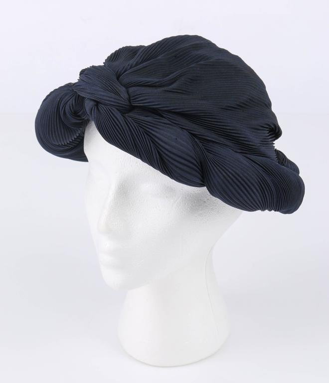 Vintage c.1930's midnight navy blue / black pleated silk turban style dinner hat. Plisse pleated silk body. Gather twisted pleat floppy brim comes to a center knot at forehead. Black silk lined and grosgrain ribbon interior rim. Almost identical