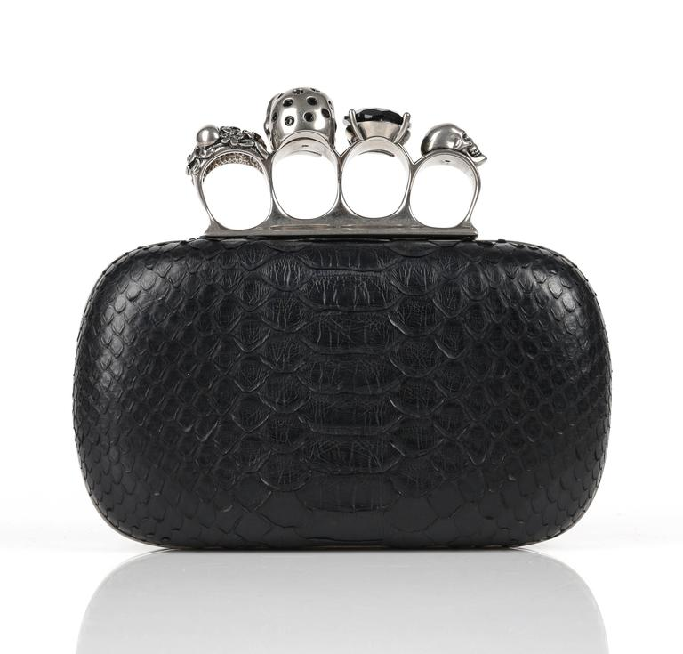 """Alexander McQueen Spring/Summer 2010 black genuine python knuckle duster box clutch. Distressed silver tone hardware. Signature hinged clasp with four """"rings"""" embellished with various skulls and swarovski crystal. Framed hard shell with rounded"""