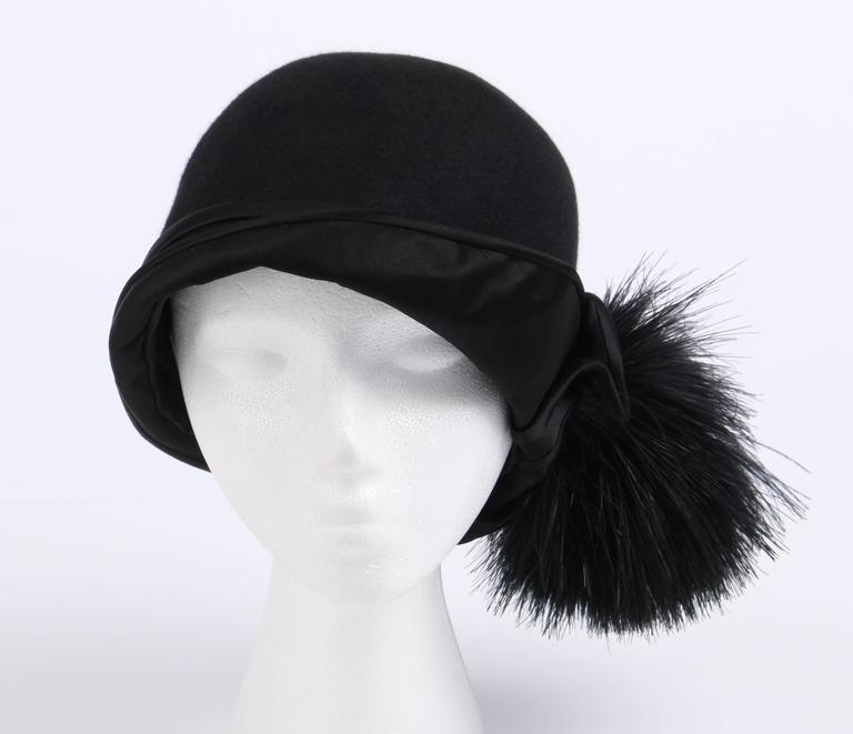 Vintage c.1920's BelArt (DH Co.) black wool / beaver felt flapper cloche hat. Bell shaped body. Turned up black satin asymmetrical brim. Large black feather pom pom embellishment attached to side of brim. Black silk lining. Unmarked Fabric Content: