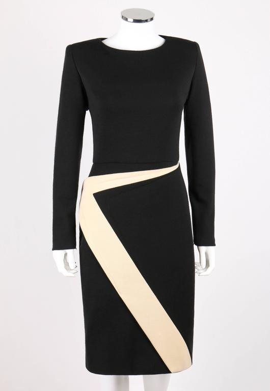 Vintage Galanos c.1980's wool knit shift dress. Black crew neckline dress. Long sleeves with zipper closures at cuffs. Ivory geometric avant garde zig zag detail from waistline to hem forming front wrap panel. Center back zipper closure with hook