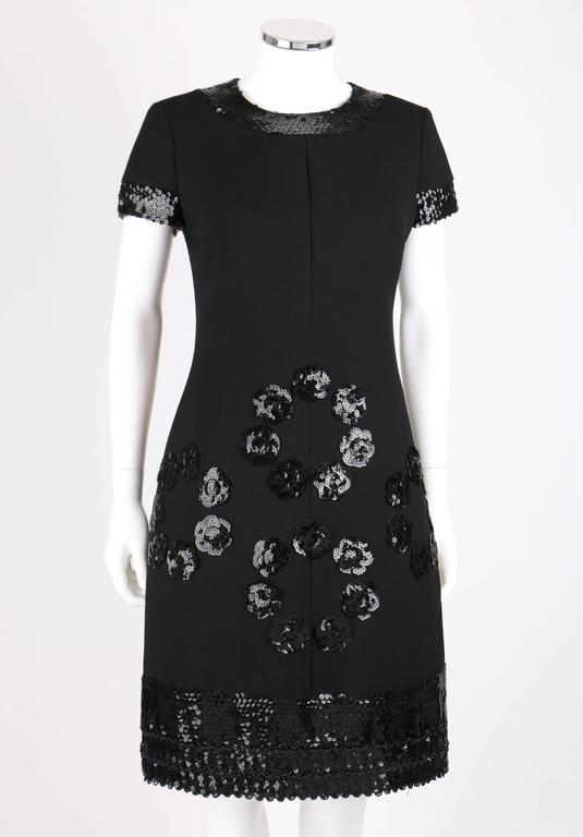 Vintage Jean Patou c.1960's black wool cocktail dress designed by Karl Lagerfeld. Short sleeves with scoop neckline. Black sequin trim along cuffs and collar with beaded scallop shaped hemline. Four clusters of sequin camellia flowers along front.