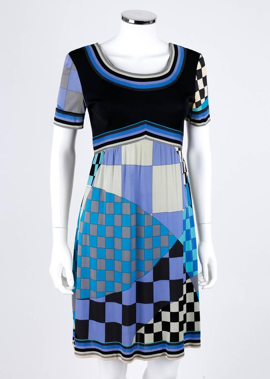 Vintage c.1960's Emilio Pucci for Saks Fifth Avenue silk jersey dress. Black bodice with short sleeves. Checkerboard signature print skirt and striped boarder trim in shades of blue, black, and gray. Empire waistline. Low scoop neckline. Side seam