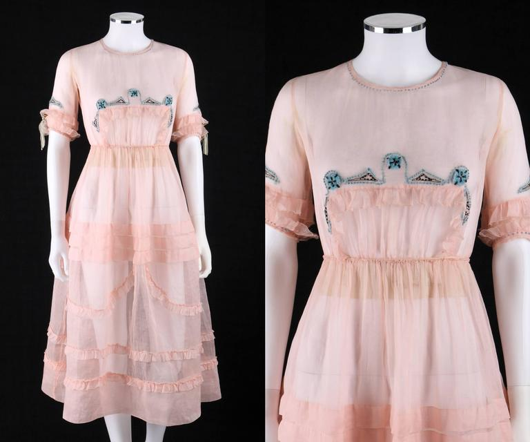 One of a Kind - Late 1910's Couture pink silk organza sheer day dress. Blue and black geometric yarn embroidered detail at collar, cuffs, and center front. Jewel neckline. Elbow length sleeves with tiered ruffles and silk bow detail at cuffs.