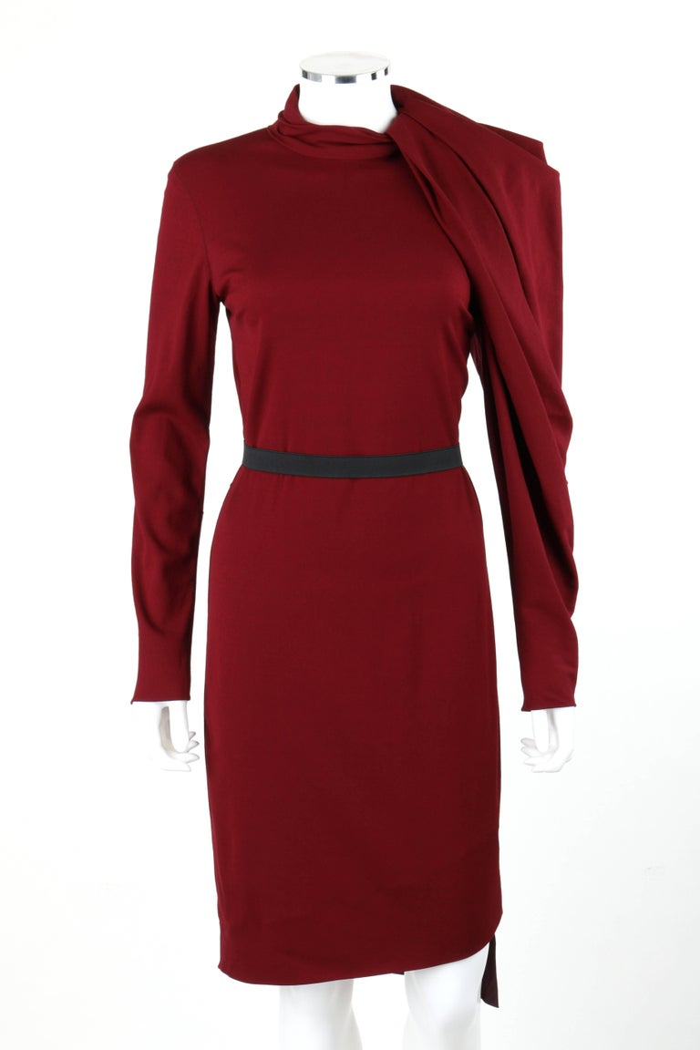 Lanvin Autumn/Winter 2011 burgundy red wool asymmetrical draped sleeve cocktail dress. Designed by Alber Elbaz. Mandarin collar with box pleat detail. Left asymmetrical long sleeve with box pleat and draped detail which wraps from left side of