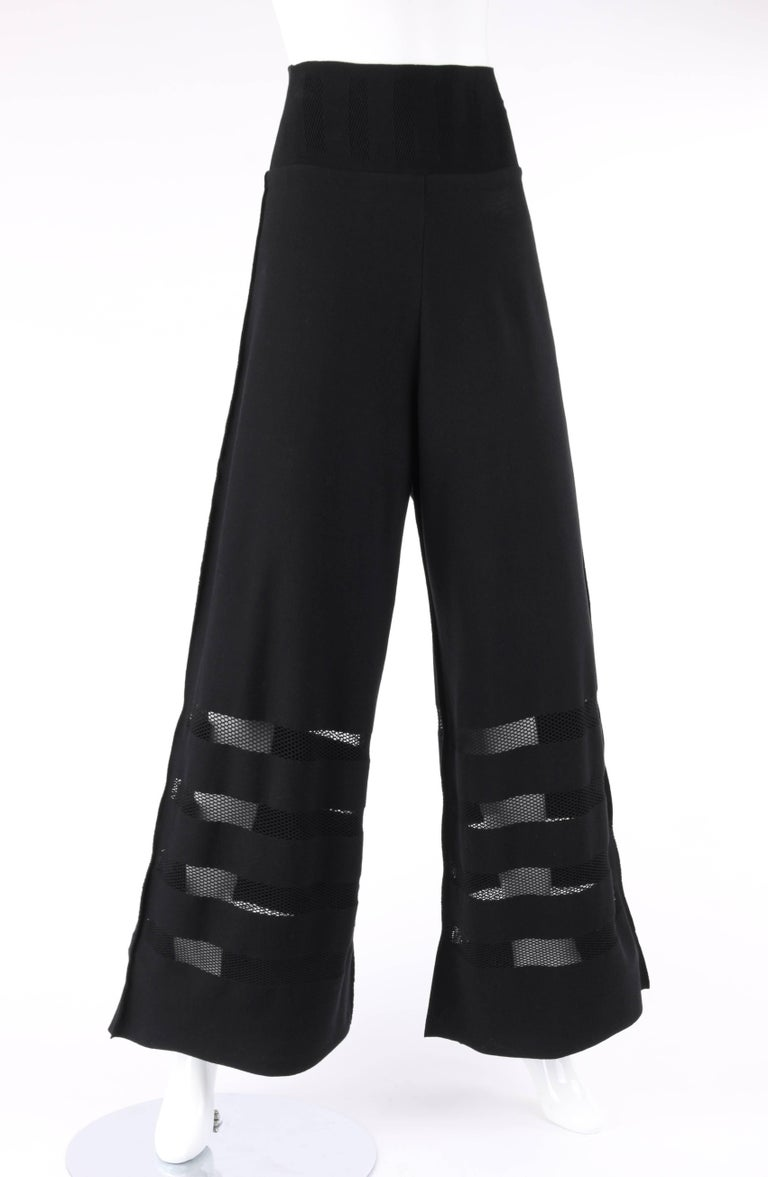 Issey Miyake A-Poc Inside black knit mesh detail wide leg pants. Designed by Dai Fujiwara. Wide yoke waistline with mesh inset detail. High waisted. Wide leg style. Four horizontal mesh panels along bottom. Raw edge detail at waistline and hem.