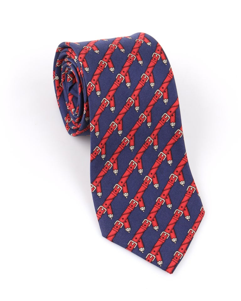 DESCRIPTION: HERMES c.1980's Navy Blue & Red Equestrian Belt 5 Fold Silk Necktie Tie 954 IA   Circa: c.1980's Label(s): Hermes; Neiman Marcus Designer: Style: 5 fold necktie Color(s): Navy blue, red, gray Lined: Yes Marked Fabric Content: 100%