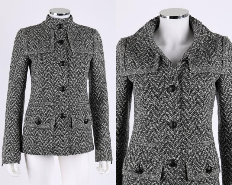 Chanel Fall 2008 wool blend black and white tweed jacket. Button down closure with Chanel logo on buttons. Dual flap detailing on shoulders. 2 button closure front pockets with welt pocket above. Elbow patches in same herringbone fabric. Zipper