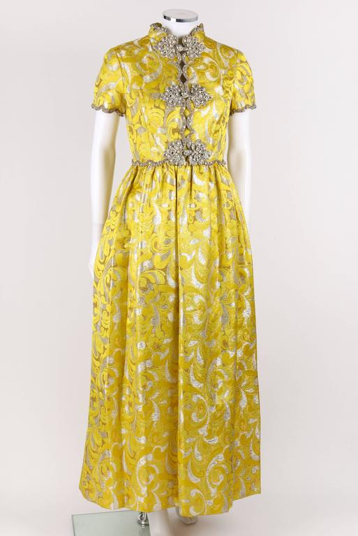 Vintage Oscar de la Renta c.1968 yellow and silver lurex brocade silk evening gown. Three gold, pearl, and crystal beaded frog closures down center front. Scalloped beaded trim around neckline, waistline, and cuffs. Two hip pockets. Short sleeve.