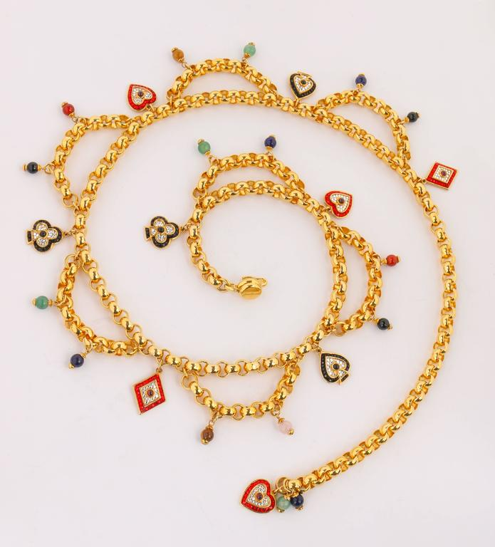 Judith Leiber gold-toned card suit charm chain belt. Gold-toned rolo chain with  rhinestone embellished heart, club, diamond, and spade charms. Draped chain sections with round multicolor stone bead charms. J hook clasp for adjustable fit. Marked: