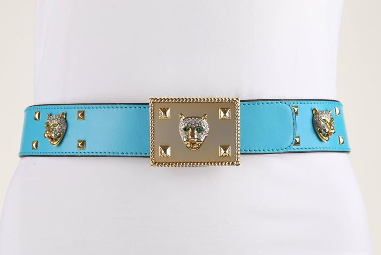 Vintage Escada c.1980's turquoise blue leather rhinestone jaguar studded belt. Turquoise leather body trimmed and backed in black leather. Embellished in gold-toned pyramid studs, jaguar heads with emerald toned eyes and rhinestone spots, and