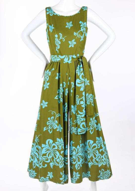 Vintage Waltah Clarke's Hawaiian Shop c.1960's floral jumpsuit. Olive green with turquoise tropical floral print. Sleeveless. Scoop neckline with low back. Gathered waistline with center front and back inverted box pleat. Wide palazzo style legs.