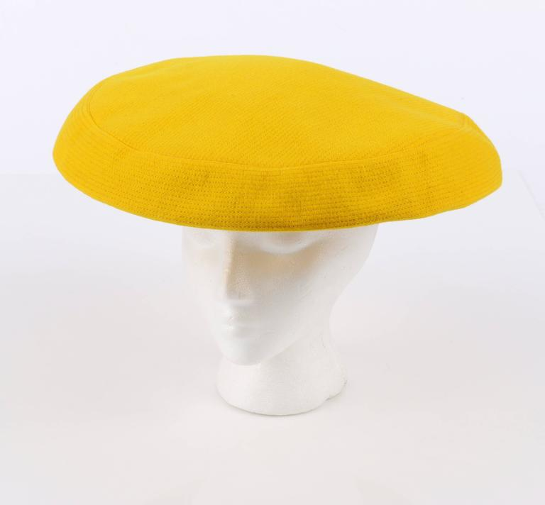 Vintage late c.1960's Yves Saint Laurent for Bergdorf Goodman yellow wool tam style hat. Yellow wool with yellow all over pin stripe top stitch detail. Wide flat top/brim. Two long wool ties with fringed ends. Elastic band at underside for snug fit.