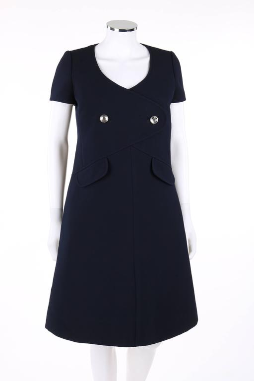 Vintage Courreges Paris for Bonwit Teller c.1960's navy blue wool a-line dress. Short sleeves. Scoop neckline. Princess seamed bodice. Faux wrap front detail with two round silver buttons. Two front mock flap pockets. Center back invisible zipper