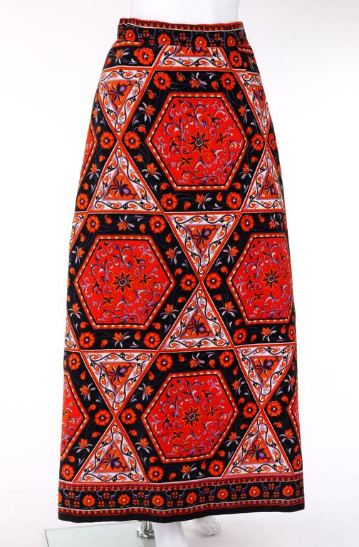 Vintage Mr. Dino c.1970's velvet print maxi skirt. Floral and geometric (hexagon and triangle) print in shades of red, orange, purple, and black. Left side seam slit. Side seam zipper and two hook and loop closures at top. Partially lined. Marked