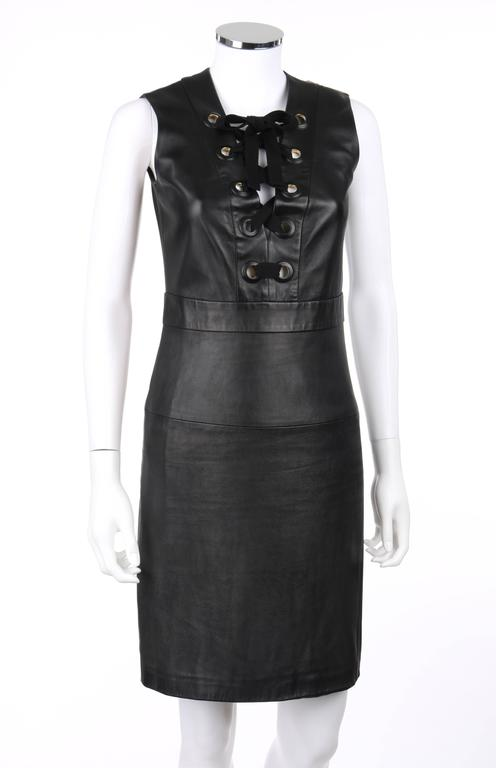 Gucci S/S 2015 black napa leather sheath dress. Deep v-neckline with black cotton twill ribbon and large leather covered grommet lace-up detail. Sleeveless. Banded waistline. Center back invisible zipper with hook and eye closure at top. Fully lined