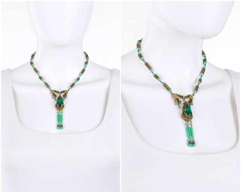 Vintage c.1920's Art Deco ornamental brass-tone and jade Czech pecking glass bead necklace. Ornamental brass-toned open work tear drop shaped pendant has large faceted emerald green crystals set in center and eleven small crystals set at top. Three