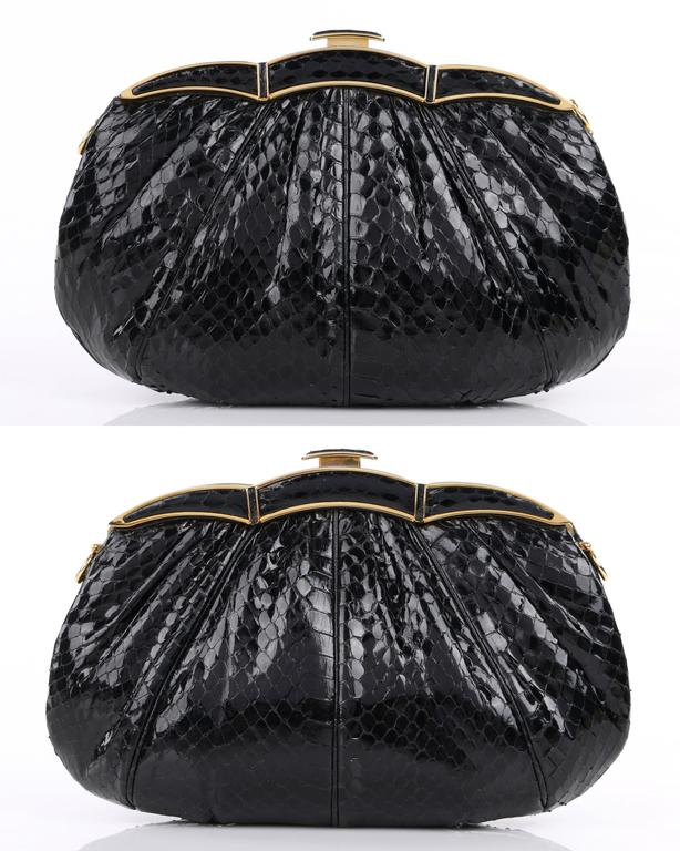 Vintage Judith Leiber c.1980's black snakeskin leather evening bag. Black glossy snakeskin exterior gathered into frame at top. Gold-toned scalloped shape frame with push top closure. Thin leather removable crossbody strap attaches with toggle