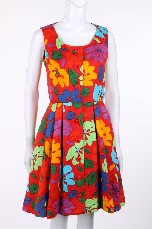 Oscar de la Renta c.1990's red multicolor floral print sleeveless dress in shades of orange, green, blue, and purple. Eight center front button closures with single hook and eye closure at waist. Scoop neckline. Knife pleated skirt. Two front inseam
