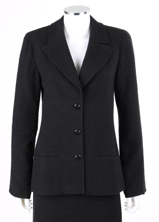 Classic Chanel Autumn/Winter 1998 two piece black boucle wool skirt suit set. Long sleeve blazer. Notched lapel collar with triple row top stitching. Three center front