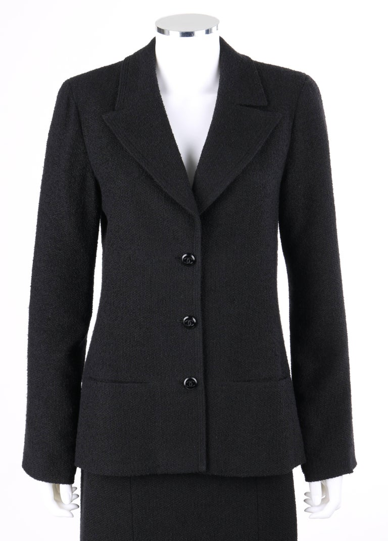 """Classic Chanel Autumn/Winter 1998 two piece black boucle wool skirt suit set. Long sleeve blazer. Notched lapel collar with triple row top stitching. Three center front """"CC"""" button closures. Two front hip pockets. Princess seams for"""