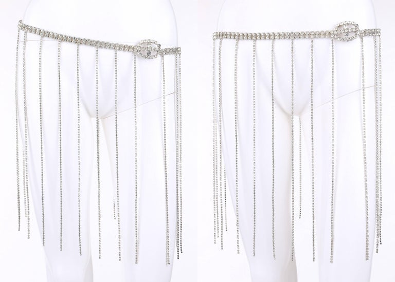 Vintage silver rhinestone 1920's flapper style fringe evening belt. Double row silver rhinestone chain body. Oval shaped rhinestone buckle with hook clasp. Twenty-four thin rhinestone fringe drops. Measurements:   Total length: 31