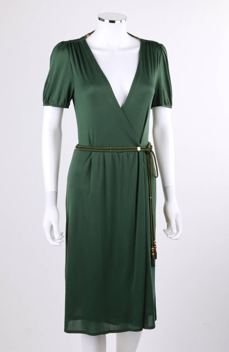 Gucci Resort 2007 forest green jersey knit wrap cocktail dress with rope belt; New with tags. Deep V surplice neckline. Short sleeves with gathered detail at cuff. Gathered shoulder seam. Back surplice neckline with green twisted double cord detail