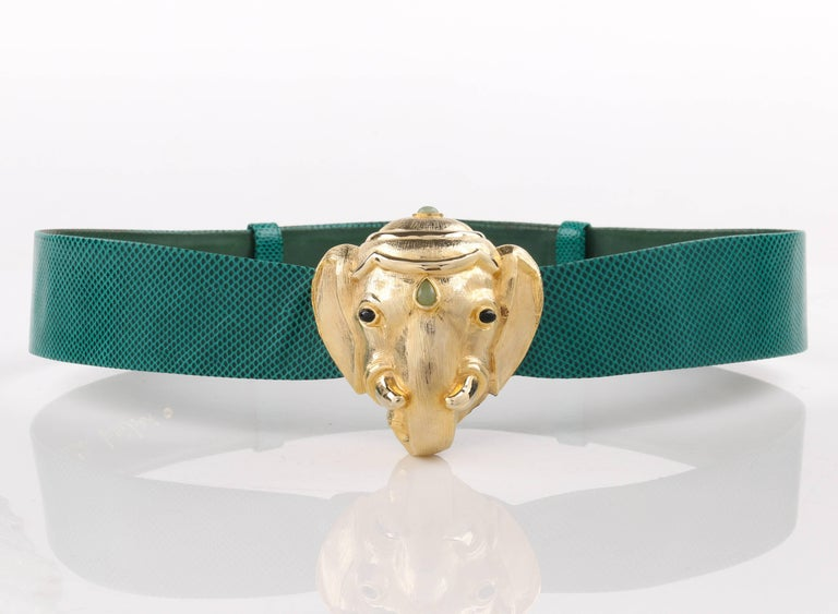 Vintage Judith Leiber c.1980's emerald green lizard skin leather gold Ganesh elephant head buckle belt. Emerald green lizard skin adjustable sliding leather body. Gold-toned metal Ganesh elephant head buckle with cabochon stones in onyx and light
