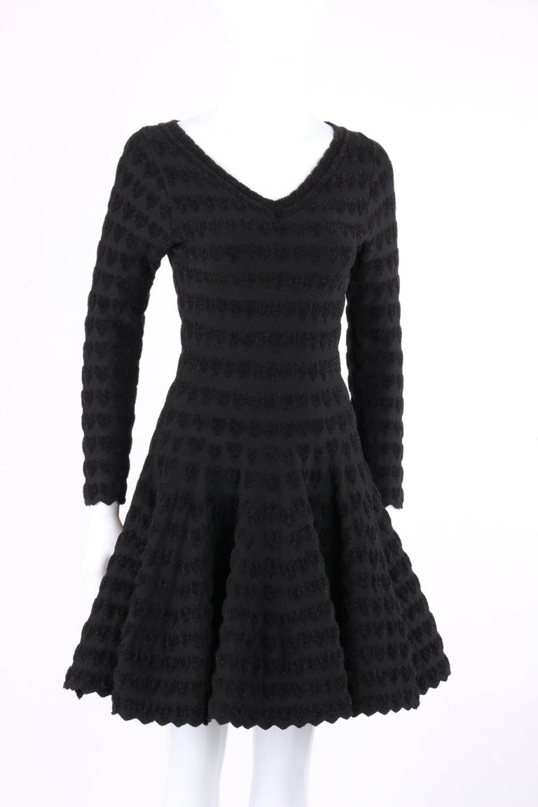 Alaia Paris black heart patterned knit cocktail dress. Black on black plush heart patterned knit. V-neckline. Long sleeves. Drop waist. Full skirt. Zigzag hem at cuffs and hemline. Slip-on. Fit and flare style. Unlined. Unmarked Fabric Content: