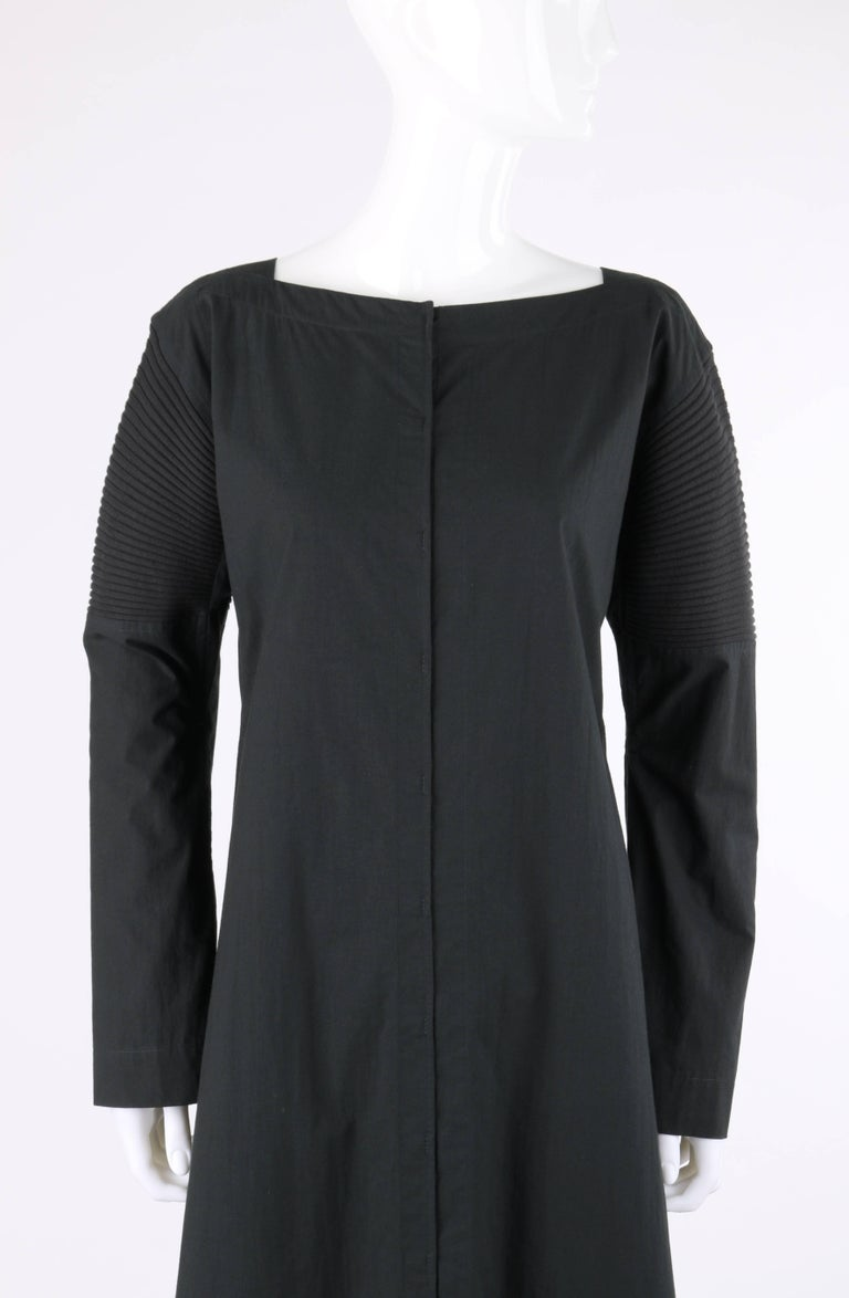 Issey Miyake black cotton rib knit detail long sleeve full length coat dress. Square bateau neckline. Drop shoulder. Long sleeves with rib knit panel from shoulder to elbow. Underarm gussets. Twelve center front concealed hook and loop closures.