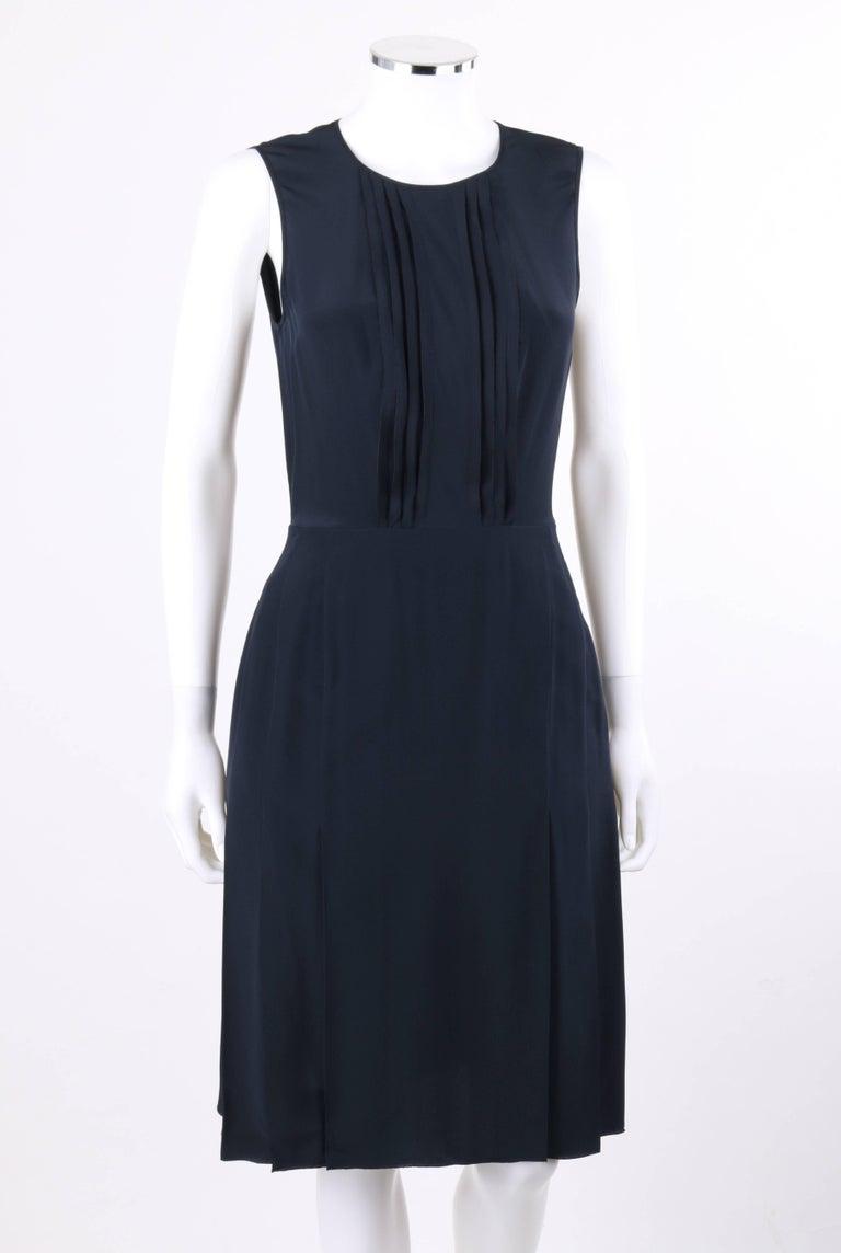 Prada navy blue silk sleeveless shift cocktail dress. Designed by Miuccia Prada. Scoop neckline. Eight center front knife pleat detail. Sleeveless shift style. Knife pleated skirt. Center back brass-toned metal exposed zipper closure. Partially