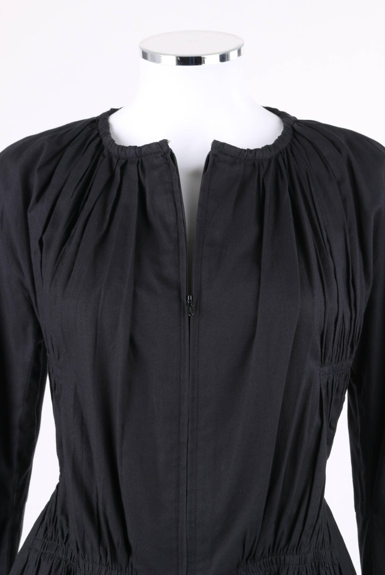 Issey Miyake black cotton gathered detail zip front jacket. Gathered scoop neckline. Long sleeves. Center front lapped separating zipper with hook and eye closure at top. Gathered detail wraps from front to back at bust, waist, and hips. Unlined.