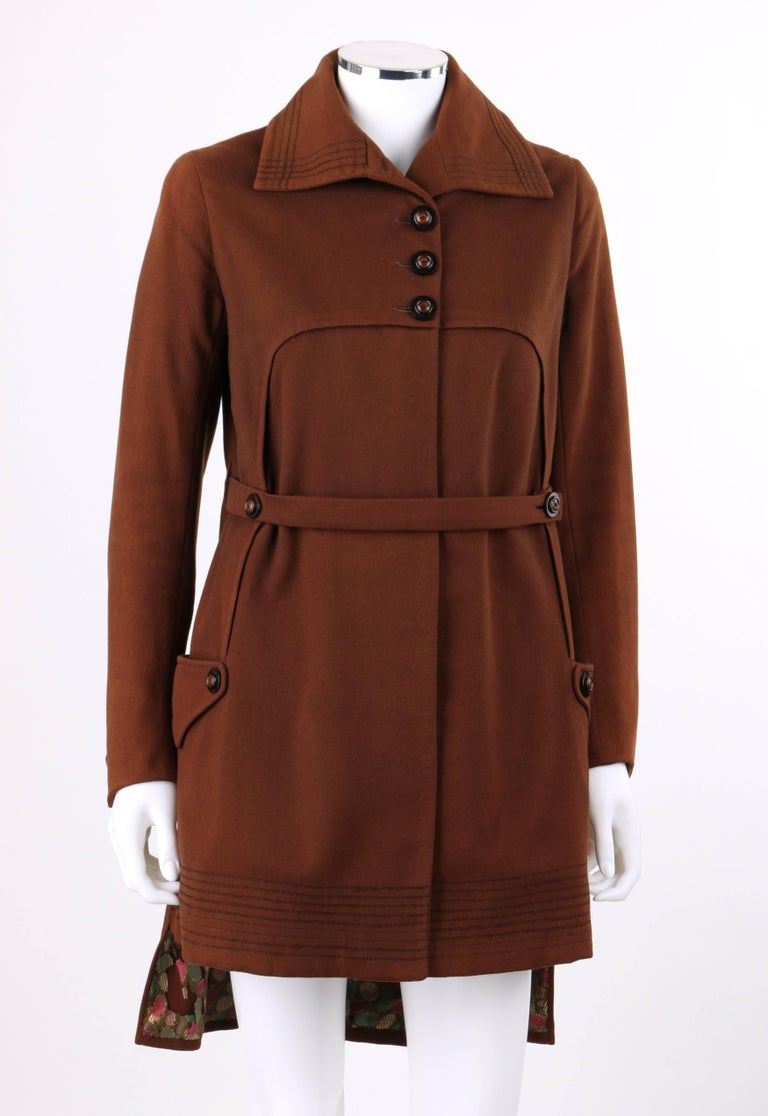 Vintage Couture c.1910's WWI brown wool belted military-cut belted coat. Bal collar with thin cord embroidered detail along edge. Five center front black and brown button closures and single snap closure at waist. Long sleeves with two button detail