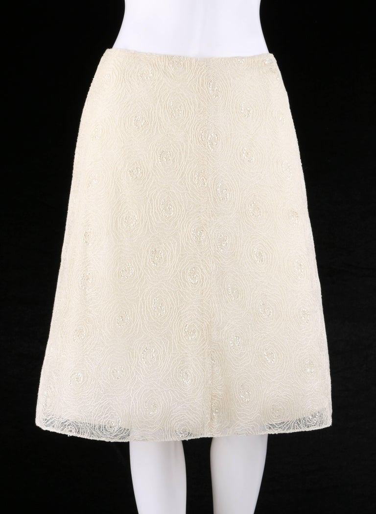 Chanel Spring/Summer 2002 cream floral embroidered sequin embellished tulle skirt designed by Karl Lagerfeld. Swirled floral embroidery over tulle net with clear sequin embellishment at center of flowers. Mother of pearl rectangular
