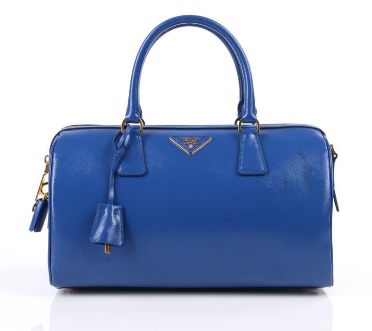Prada Spring/Summer 2012 blue saffiano vernice (patent) leather convertible Boston bag. Designed by Miuccia Prada. Blue (azzurro) saffiano vernice leather structured body. Two single rolled top handles with gold-toned metal d-ring hardware. Piped