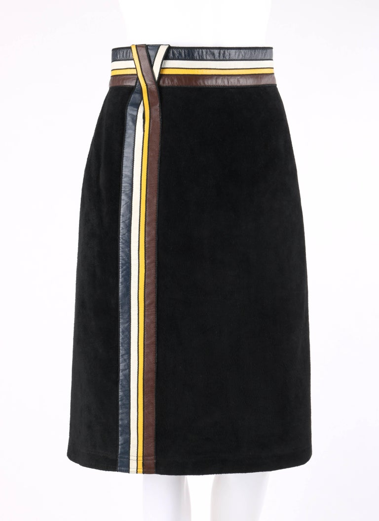 Vintage Pierre Cardin c.1960's black suede leather striped detail knee length skirt. Black suede leather shell. Navy blue, off white, yellow, and brown striped leather applique at waistband and side front of skirt. Center back zipper closure with