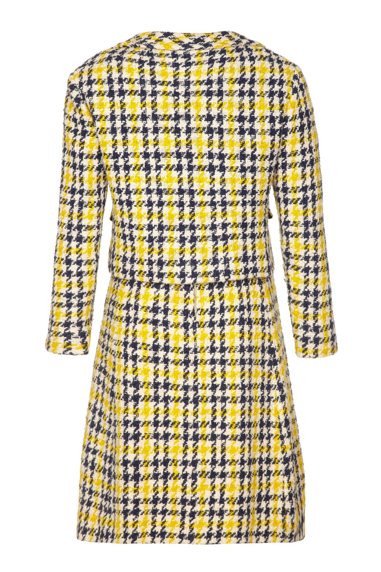 A really great little 60s number this two piece suit is made up of yellow, blue and cream tartan jacket and sleeveless dress with yellow bodice.  The jacket fastens at the front with lovely gold buttons that are also featured on the faux hip