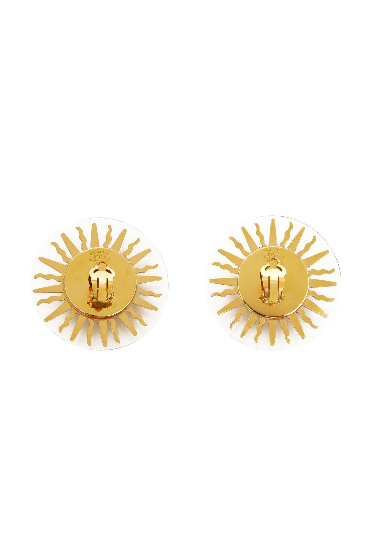 Fabulous Chanel clip on earrings consisting of clear resin disc with gold tone metal sun decoration.  They are marked on the back as being from season 24 dating them 1985.  Loads of fun for any occasion, they are in excellent